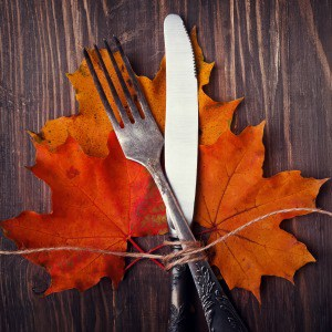 Autumn table setting with leaves. Dark toned photo