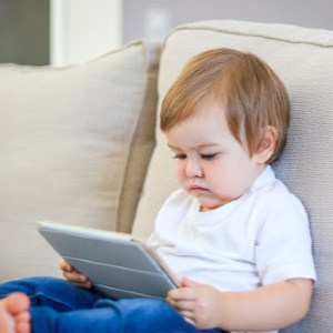 Cute little baby watching cartoon on digital tablet sitting on the sofa. Parenting control. Child internet safety concept.