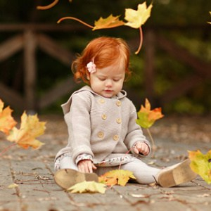 Red-haired baby girl on the background of nature and sitting in the fall leaves