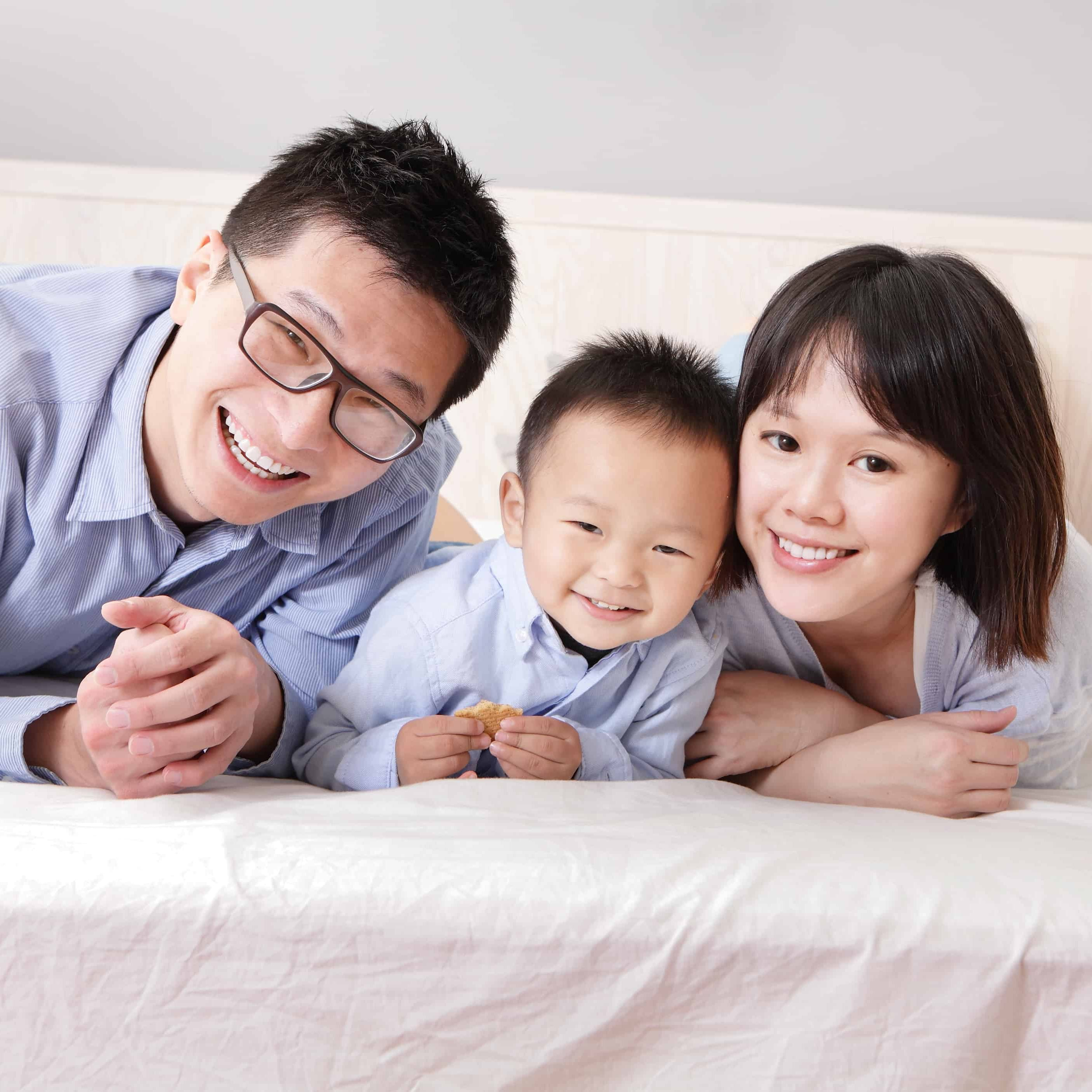 A happy family lying on white bed in the bedroom with gray wall for copy space, asian people